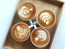 Lattekonstkaffe som så är läckert på trä Fotografering för Bildbyråer