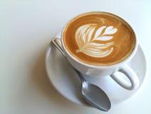 Lattekonstkaffe som så är läckert på vit Arkivfoto