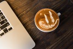 Lattekonstkopp på trätabellen med tangentbordet av bärbara datorn Arkivfoto