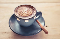 Lattekunst, blaue Kaffeetasse auf grauem Hintergrund Lizenzfreie Stockbilder