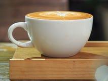 Lattekunst ist auf hölzerner Untertasse stockfoto