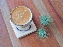 Lattekunstkaffee auf der hölzernen Untertasse Stockfoto
