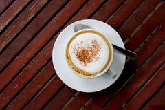 Lattekunstkaffee auf hölzerner Tabelle lizenzfreies stockfoto