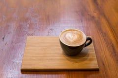 Lattekunstkaffee auf hölzerner Tabelle lizenzfreie stockbilder