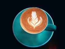 Lattekunstkaffee in der grünen Schale auf schwarzer Tabelle Stockfotografie