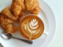 Lattekunstkaffee so köstlich mit Hörnchen auf Weiß Stockbild