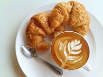 Lattekunstkaffee so köstlich mit Hörnchen auf Weiß Lizenzfreies Stockfoto