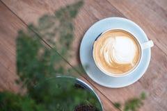 Lattekunstkaffee mit Baum in einer weißen Schale auf hölzernem Hintergrund Stockfotografie