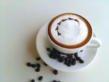 Lattekunstkaffee mit der Kaffeebohne so köstlich auf Weiß Stockfoto