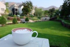 Lattekunstkaffee mit schöner Ansicht in grünes Yard und in Berg lizenzfreie stockbilder