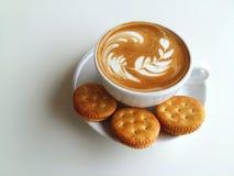 Lattekunstkaffee und -cracker so köstlich auf Weiß Lizenzfreie Stockfotos