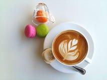 Lattekunstkaffee und -makronen so köstlich auf Weiß Stockfotos