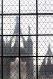 Lattice of square iron rods window of old european palace. Lattice of square iron rods with View through window to an old european palace Stock Photography