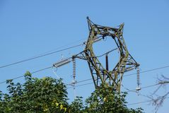 Lattice-type steel tower fragment over blue sky as a part of high-voltage line. Overhead power line details.  stock image
