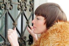 Lattice window. Woman in red fur coat holding lattice of window stock image