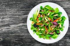 Lattuga mista, spinaci, carota, prosciutto, formaggio e prugne insalata, superiore vista fotografie stock