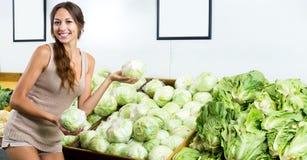 Lattuga verde fresca di compera della donna positiva Fotografia Stock Libera da Diritti