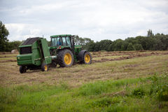 Latvia - August 6.2017: John Deere tractor collecting hay of dry grass after mowing on the meadow field in the end of summer Royalty Free Stock Photos