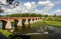 latvia Ciò è un vecchio ponte sopra il fiume Immagine Stock