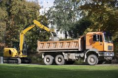 Latvia. Excavator loads trash. In a park onto a truck stock photo