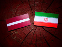 Latvia flag with Iranian flag on a tree stump isolated Stock Image