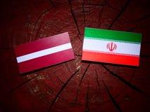 Latvia flag with Iranian flag on a tree stump isolated. Latvia flag with Iranian flag on a tree stump Stock Image