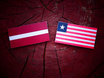 Latvia flag with Liberian flag on a tree stump isolated. Latvia flag with Liberian flag on a tree stump Royalty Free Stock Photos