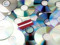 Latvia flaga na górze cd i DVD stosu odizolowywającego na bielu Obraz Royalty Free