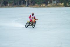 Latvia, Raiskums, Winter motocross, Driver with motorcycle, race. Lake. 2015 Royalty Free Stock Photography