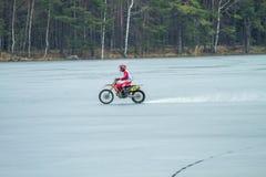 Latvia, Raiskums, Winter motocross, Driver with motorcycle, race. Lake. 2015 Stock Image
