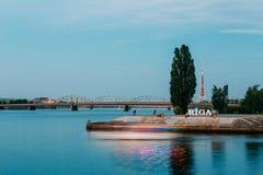 latvia Riga Bulwar Przy Daugava rzeką Z miasta imienia znakiem, Odpoczynkowi ludzie Wokoło Zdjęcie Stock
