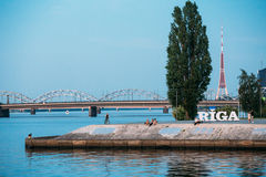 latvia riga Invallning på Daugavafloden med stadsnamntecknet, arkivbild