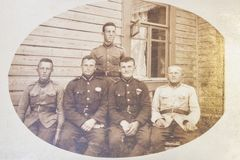 Latvia - 1930s: An antique photo shows five soldiers posing in front of wooden house.  royalty free stock images