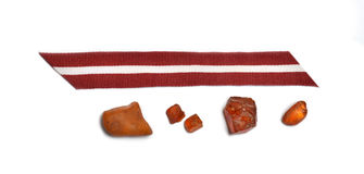 Latvia's flag ribbon and amber pieces Royalty Free Stock Images