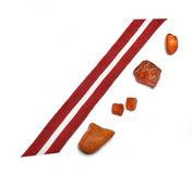 Latvia's flag ribbon and amber pieces Royalty Free Stock Photos