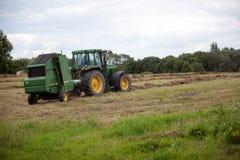Latvia, Sierpień - 6 2017: John Deere ciągnikowy zbieracki siano sucha trawa po kosić na łąkowym polu w końcówce lato Zdjęcia Royalty Free