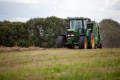 Latvia, Sierpień - 6 2017: John Deere ciągnikowy zbieracki siano sucha trawa po kosić na łąkowym polu w końcówce lato Zdjęcie Royalty Free