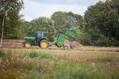 Latvia, Sierpień - 6 2017: John Deere ciągnikowy zbieracki siano sucha trawa po kosić na łąkowym polu w końcówce lato Zdjęcie Stock