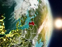 Latvia during sunrise. Highlighted in red on planet Earth with visible country borders. 3D illustration. Elements of this image furnished by NASA Royalty Free Stock Photography