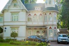 Latvia tall house made of wood. Jurmala, Latvia wooden big house and cars near it Royalty Free Stock Photography