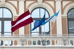 Latvian-, EU- und Riga-Flaggen auf der Fassade lizenzfreie stockfotos