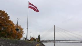 Latvian flag in autumn. And Vansu bridge in background stock video footage