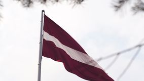 Latvian flag fluttering in the wind high up in the sky during a Golden Hour sunset - Riga capital, Latvia - Dambis AB. Huge country national flag - April `19 stock video footage