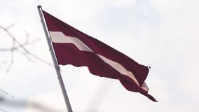 Latvian flag fluttering in the wind high up in the sky during a Golden Hour sunset - Riga capital, Latvia - Dambis AB