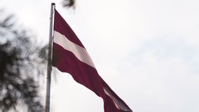 Latvian flag fluttering in the wind high up in the sky during a Golden Hour sunset - Riga capital, Latvia - Dambis AB. Huge country national flag - April `19 stock video
