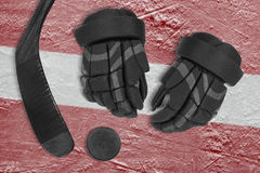 Latvian flag, hockey puck, gloves and putter Stock Photography