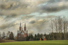 Latvian village field with tractor Royalty Free Stock Image