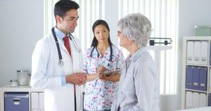 Latynosa doktorski opowiadać z starszym pacjentem Zdjęcia Stock