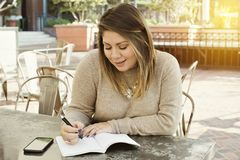 Latynoska kobieta ono Uśmiecha się Pisze puszkowi Jej ćwiczenie celach w czasopiśmie przy Plenerowym Cafre Podczas gdy obraz royalty free