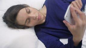 Latynoska kobieta Używa Smartphone przy nocą, Scrolling ekran zbiory